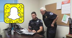 Officer Chrissy looking at phone with snapchat logo