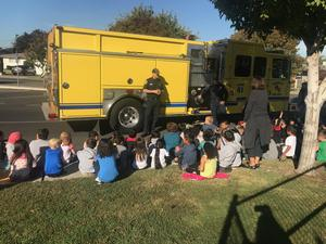 firetruck with two firemen in uniform presenting to young students