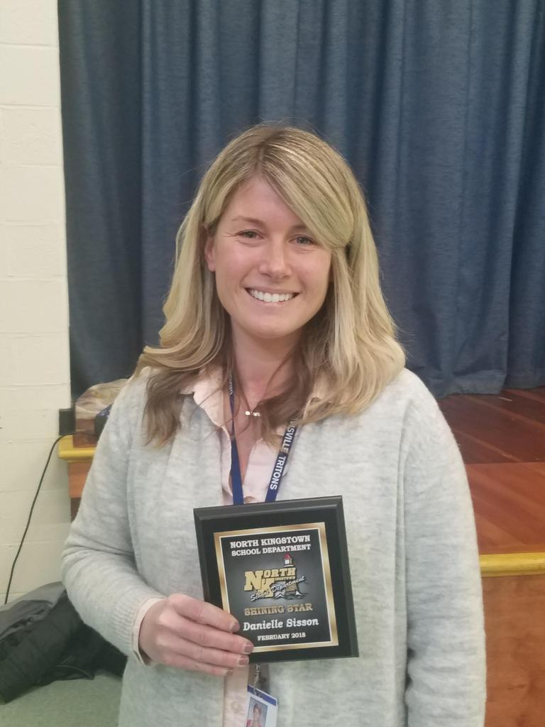 Teacher holding award