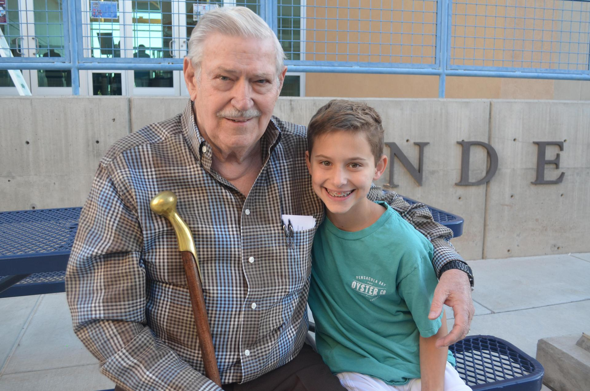 Student smiles with grandparent