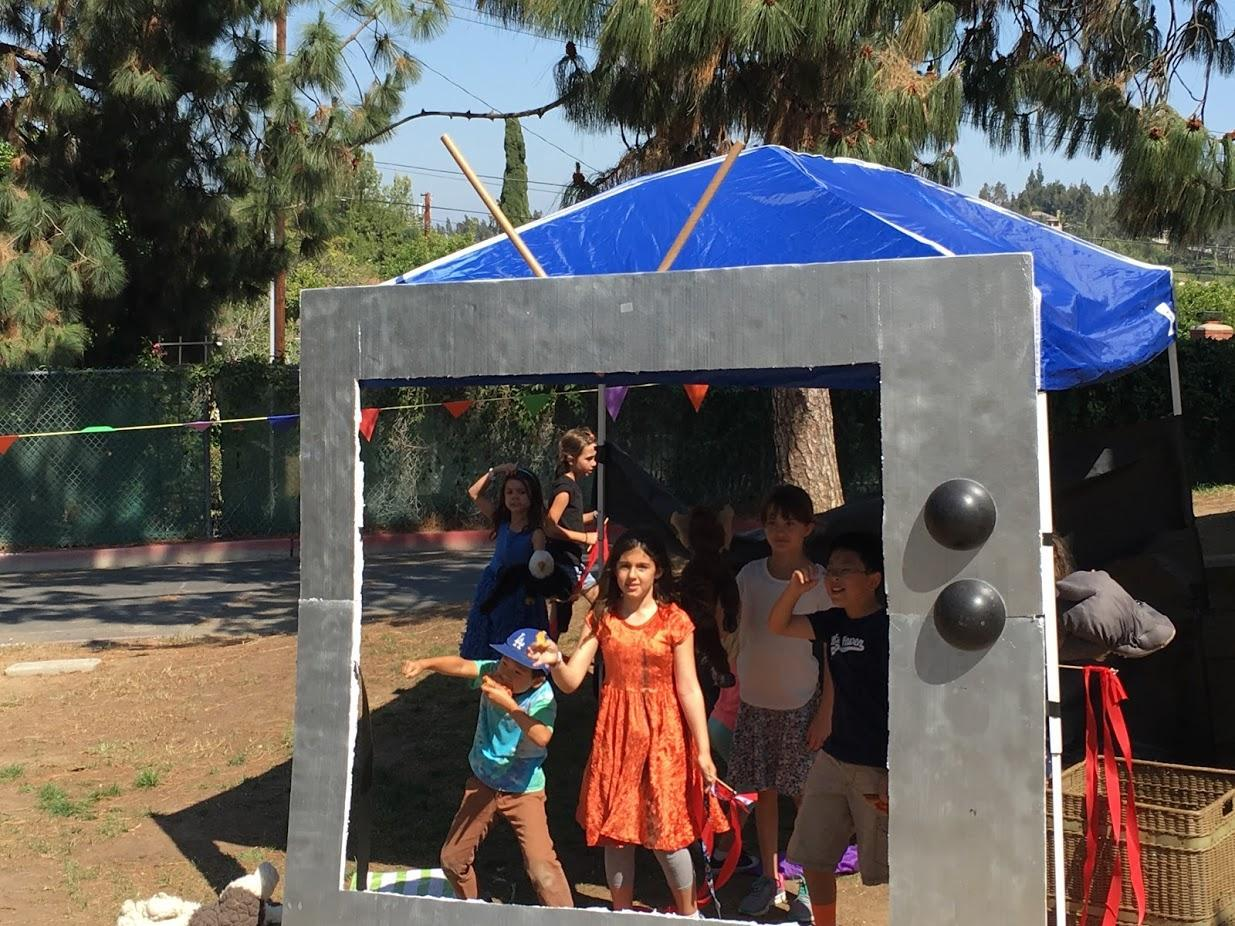 Children created TV frame out of recycled materials for imaginary play.