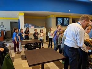 students in line for desserts served by Chef