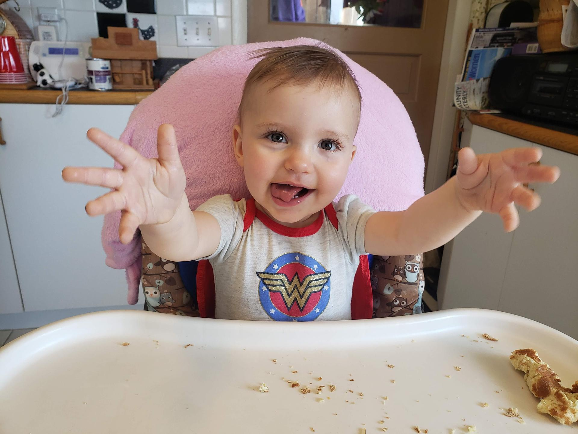 Baby in high chair smiles while sticking tongue out, wearing a Wonder Woman shirt, and holding arms out to camera