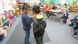 Two boys act out a vocabulary word in front of the class.
