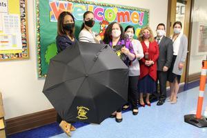 Teachers posing with Jefferson Jaguar umbrella outside