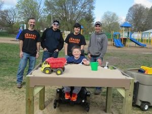 Kindergarten student Nathan was surprised with a new sandbox built for wheelchair accessibility. Pictured with him are TKHS woods teacher Matthew Melvin and high school woods students Collin Wright, A.J. Ricco and J.C. Rose.