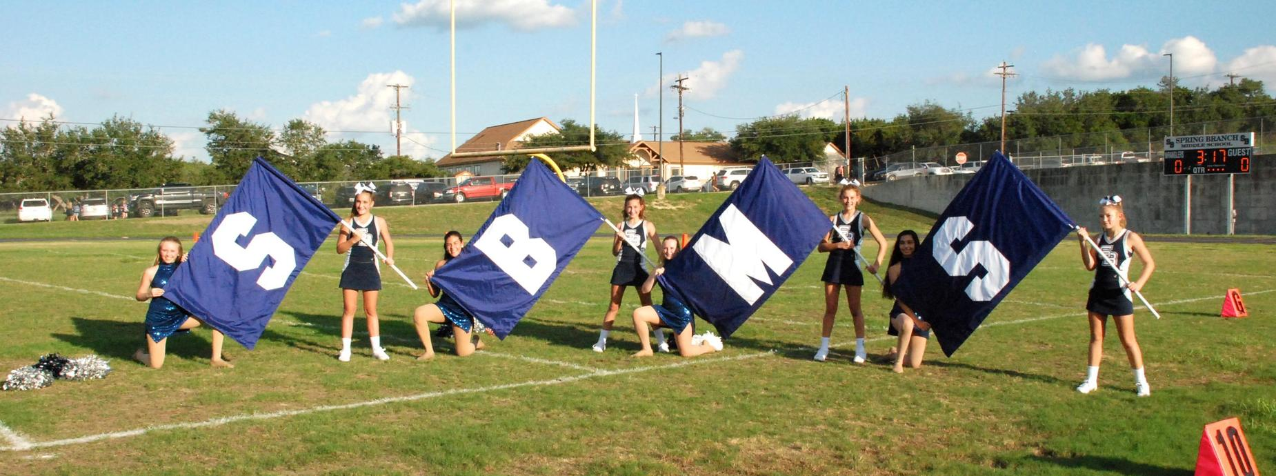 Cheerleaders holding SBMS flags