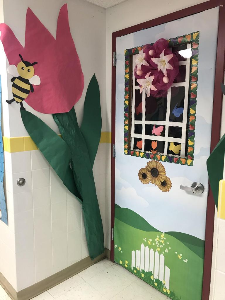 large pink tulip flower with a bee and a spring door display