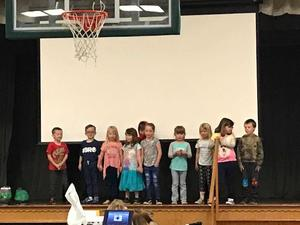 Kindergarten students on stage singing the alphabet in Spanish.