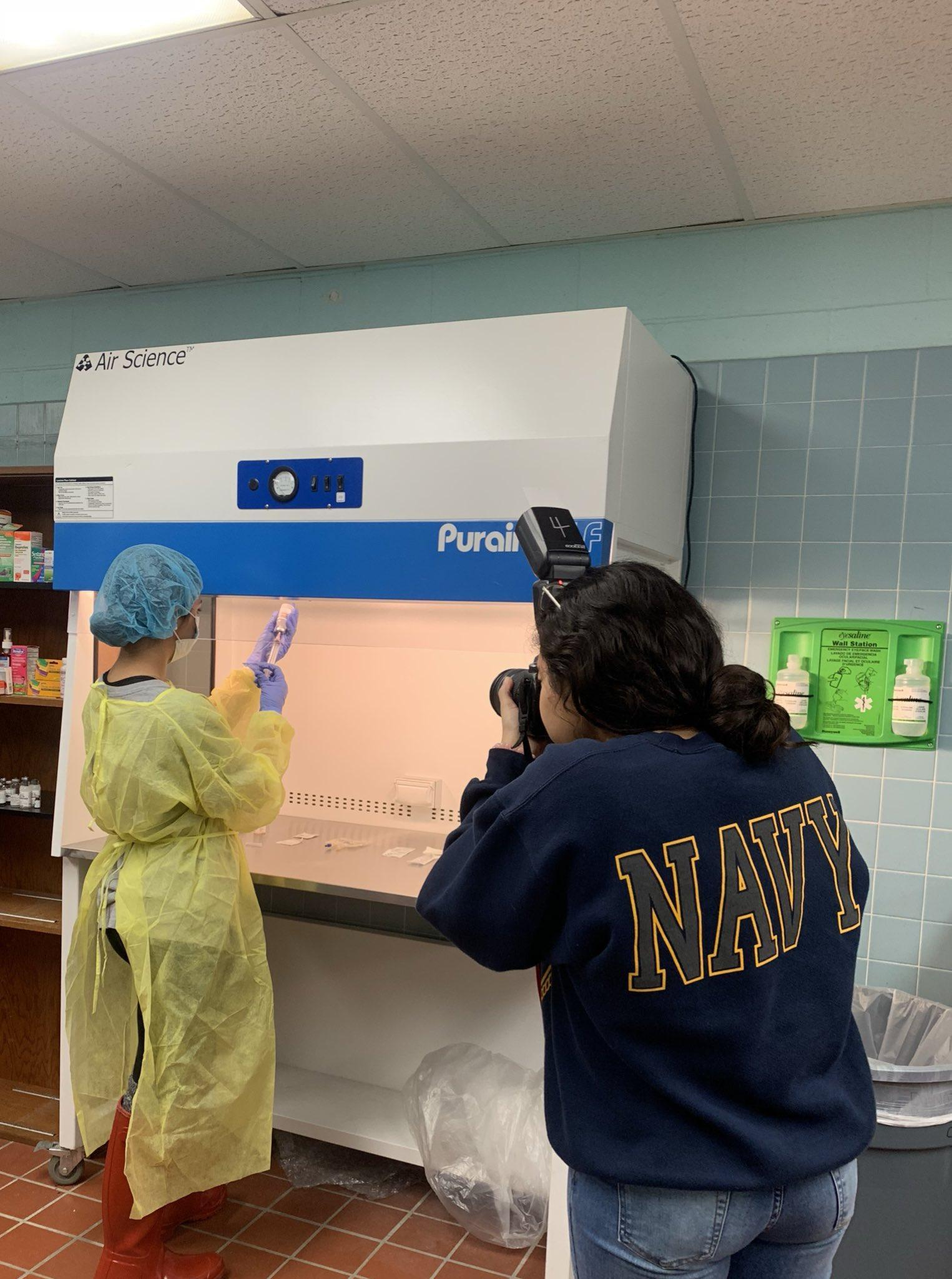 student taking picture of another student in apron in front of fume hood