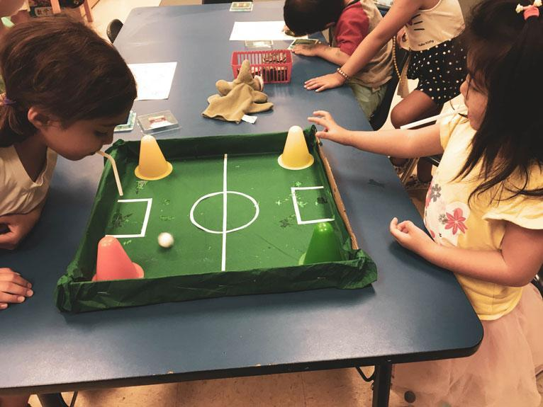 aHWIS Immersion Summer Camp HudsonWay Olympians Play at a Table