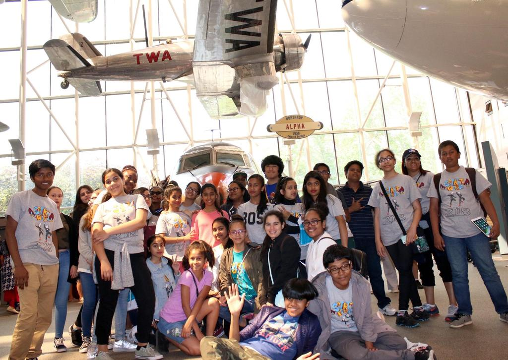 M.S.80 students posing in front of an old airplane