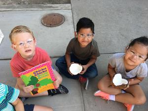 3 students holding Chicka Chicka Boom Boom and a coconut broken open