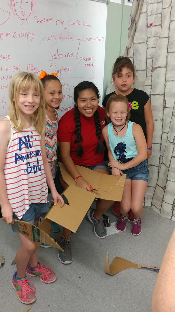 Smiling for the camera while cutting the cardboard for their project