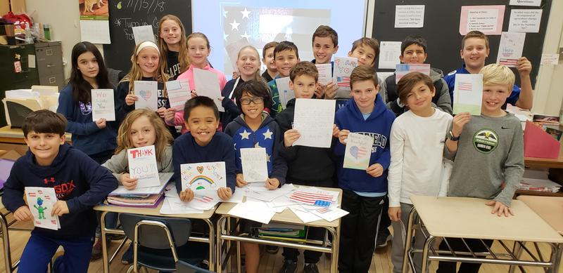 Students at Roosevelt Intermediate School hold cards and letters they wrote for troops serving overseas to brighten their holidays.
