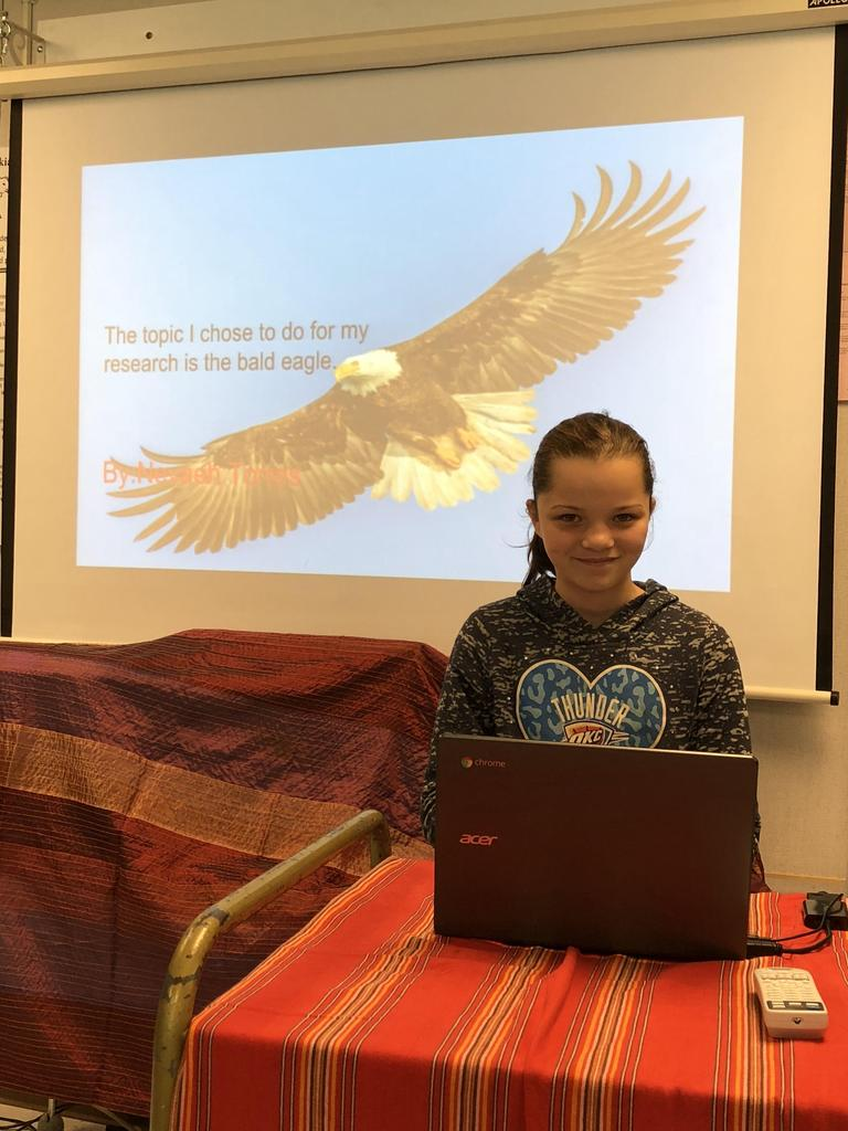 "Student picture with presentation slide ""Bald Eagle"" in the back"
