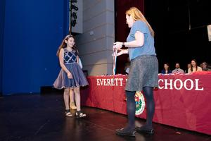 A student walks across the stage to accept a medal from a teacher