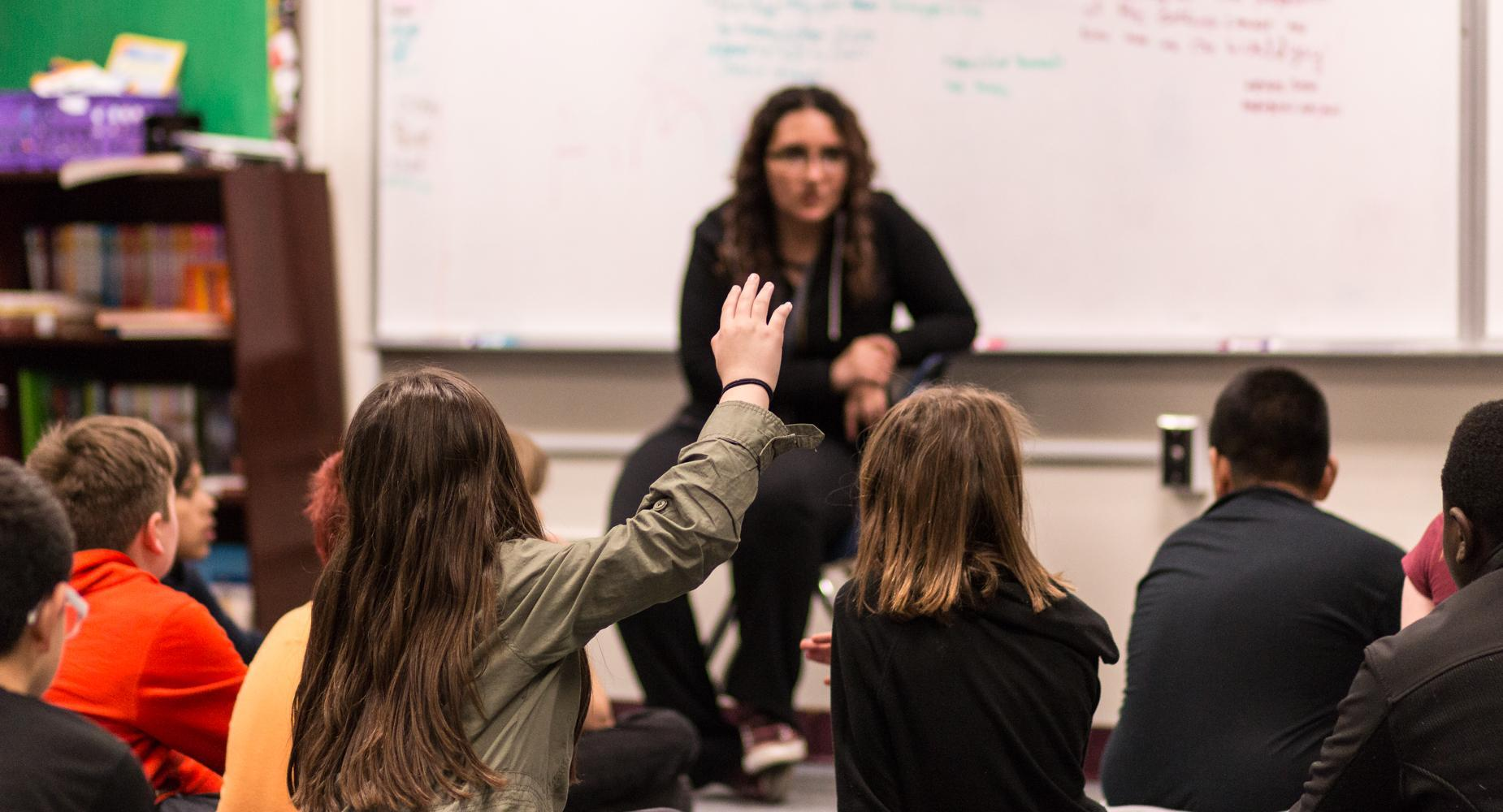 Teacher talks with children sitting on floor