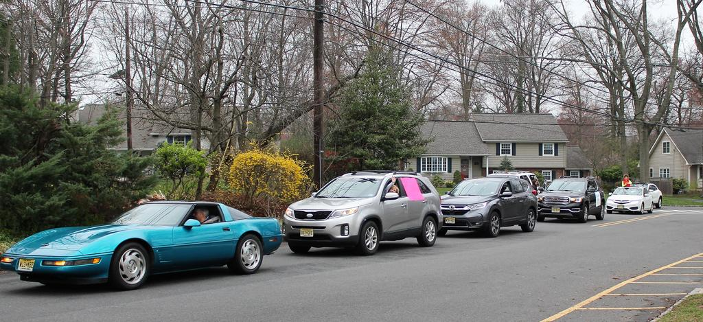 Photo of Washington teachers waving to families during a car parade for students during COVID-19 distance learning.