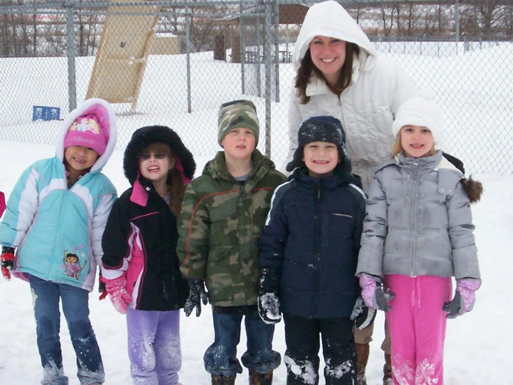 kids outside in snow at recess with teacher