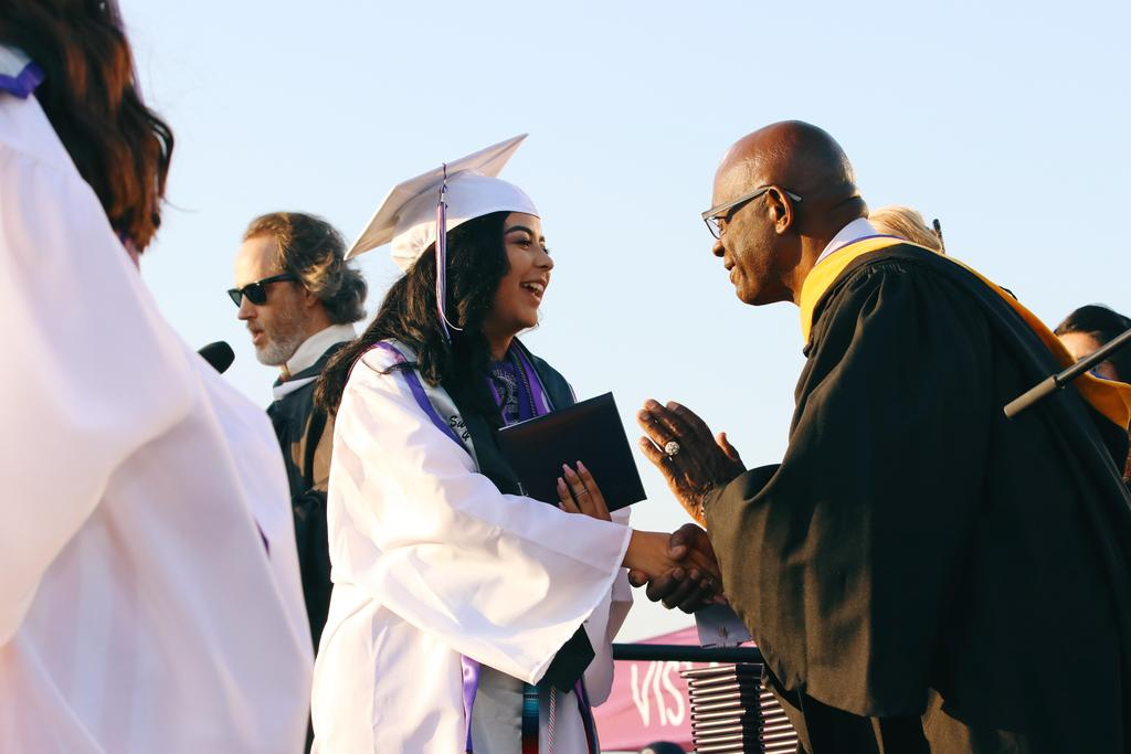Board of Education Clerk Cleveland Johnson congratulates graduate