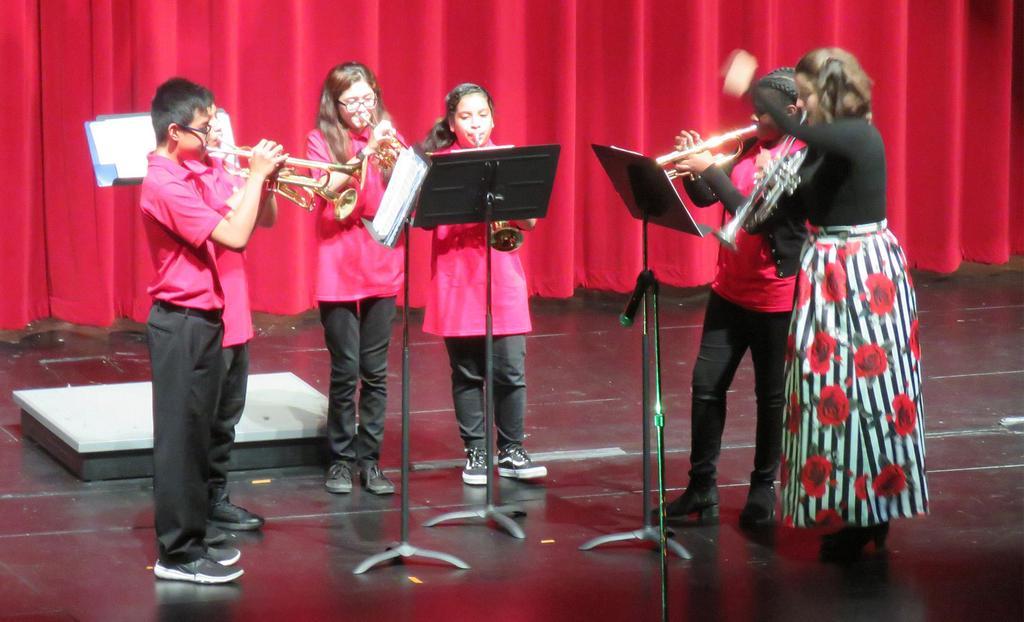 A teacher conducts four brass players
