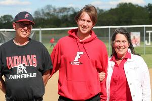 A photo of a senior softball member and his parents.