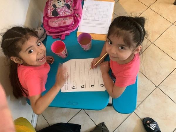 two girls at a little table writing the letter A together