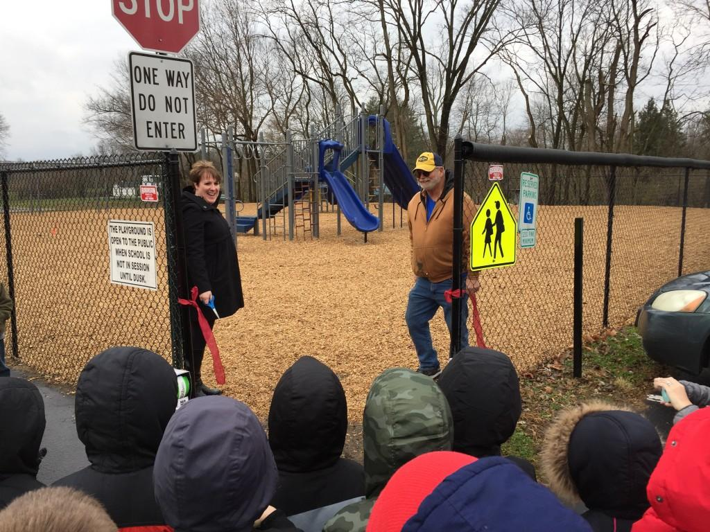 Mrs. Harrison and Mr. Fisher cut the ribbon to the new playground.