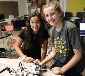 Two STEM campers build a robot during STEM Camp.