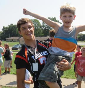 A TKHS varsity football player finds a friend at Lee Elementary.