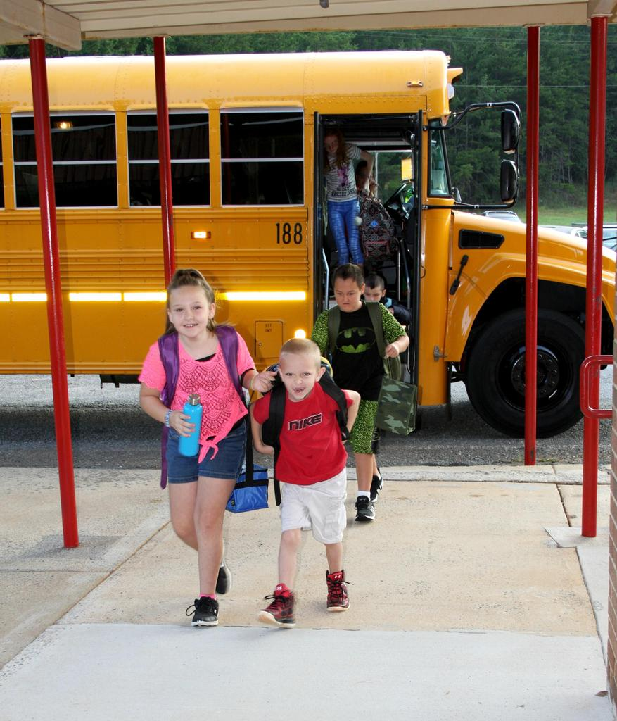 Students unload from the school bus on the first day of school at C.B. Eller Elementary.