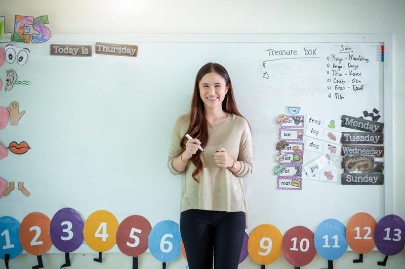 female teacher smiling while standing in front of white board in classroom