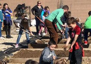 Children work to prepare the garden beds.