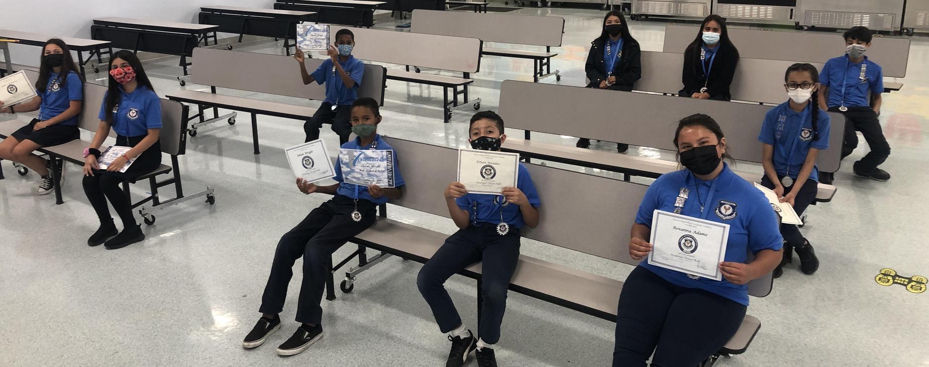 students sitting displaying certificates