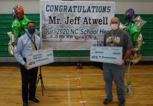 Mr. Atwell and Mr. Graham hold large award checks at celebration ceremony