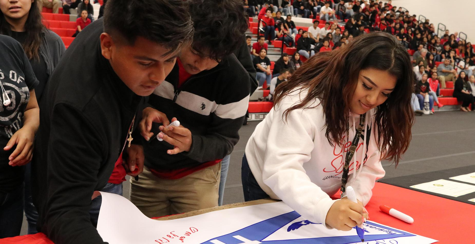 Students sign posters