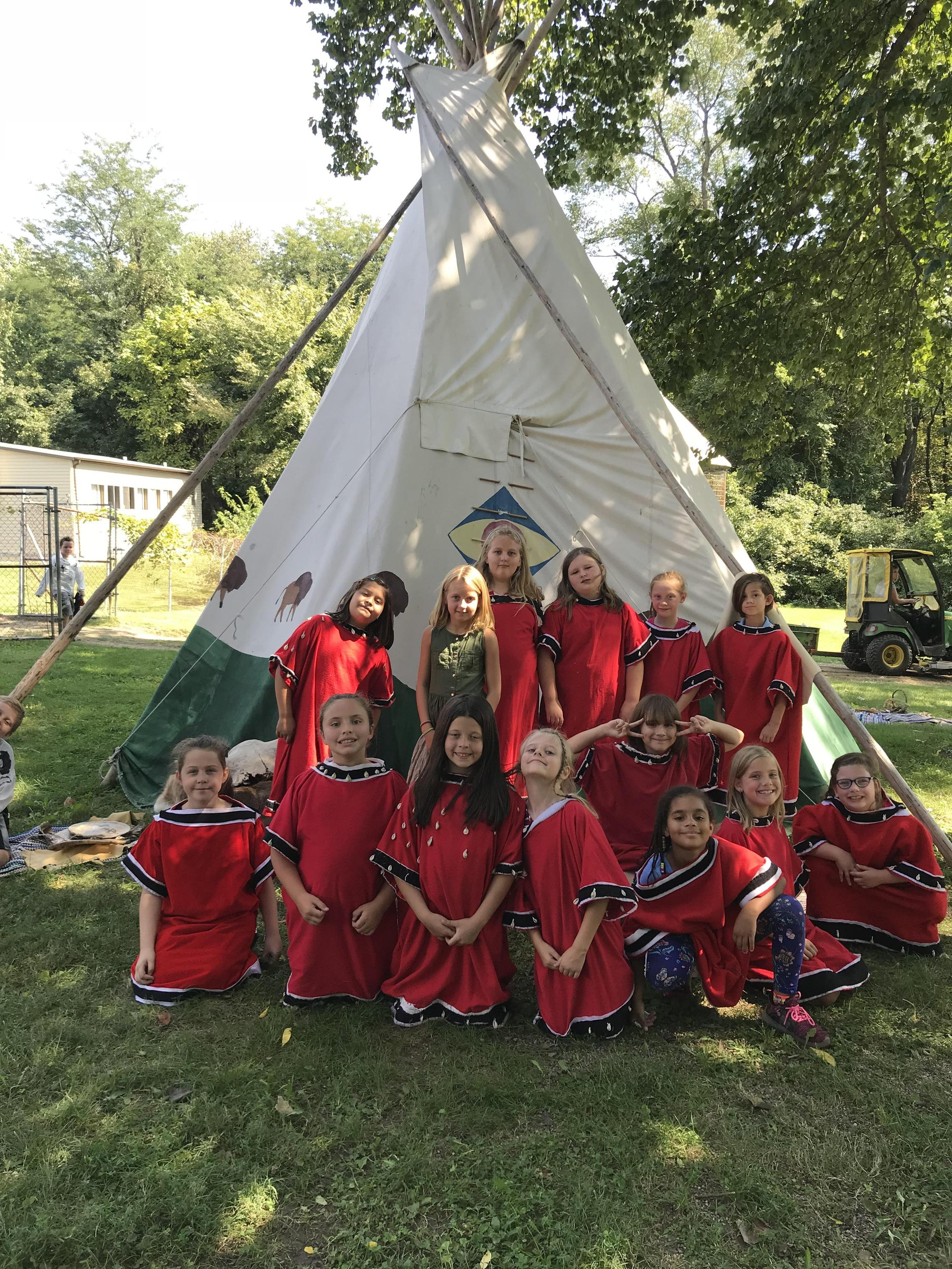 Students dressed as Native Americans in front of a TiPi.