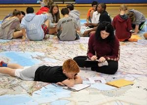 In a geo-scavenger hunt, of sorts, students used latitude and longitude to find an assigned location on the National Geographic Giant Map, set up in the schools' gymnasiums. Once at the location on the map, the students found an envelope with instructions on how to proceed with their lesson on European History.  Pictured here are RIS students grouped and studying on the Giant Map.