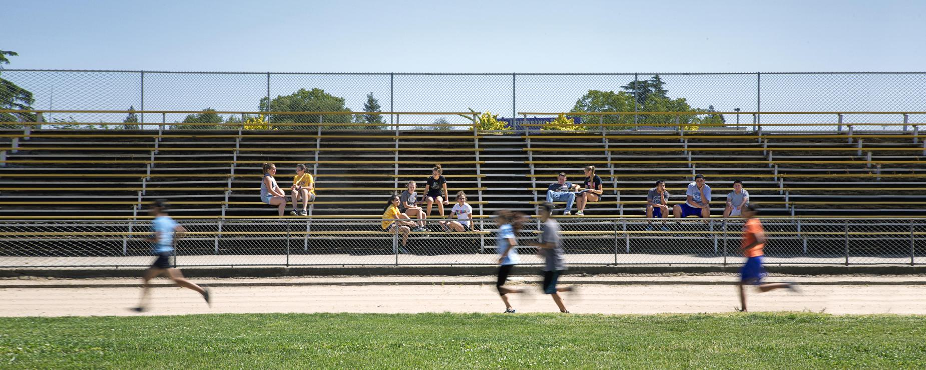 Students running around track while students watch from stands