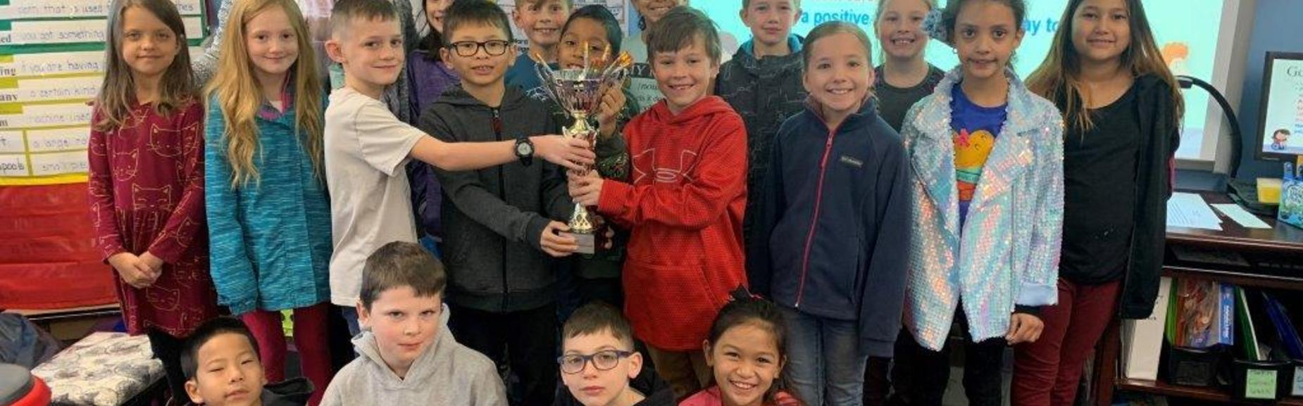 students holding attendance trophy