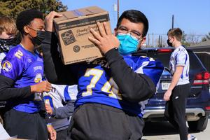 football player hands out food