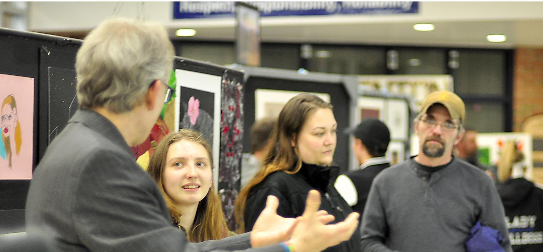 Superintendent bills speking with one of our Senior Artists and the Senior Art Exhibition