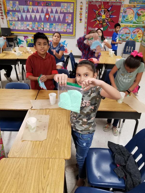 Student displays slime creation in ziploc bag.