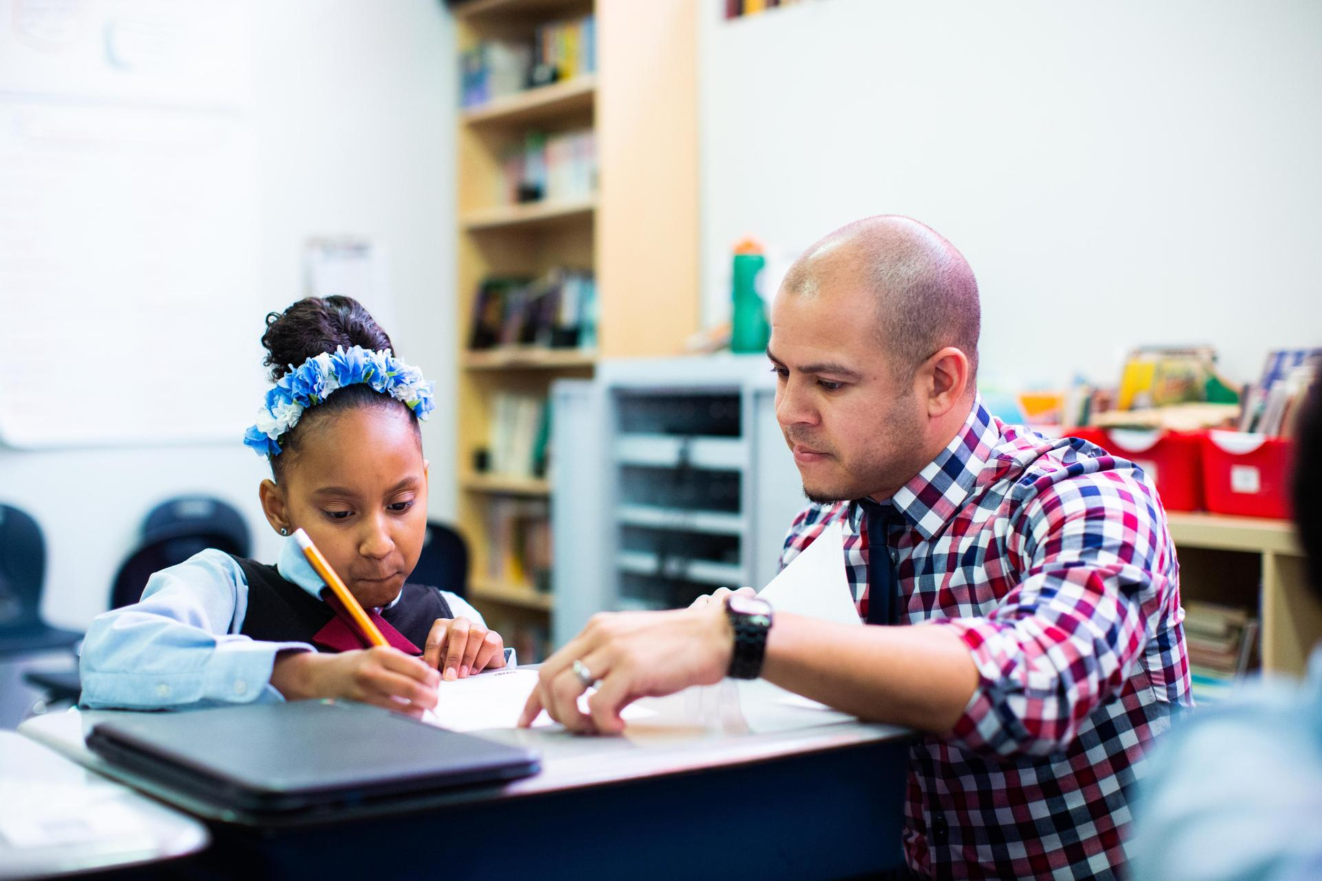 teacher kneeling next to student who is writing