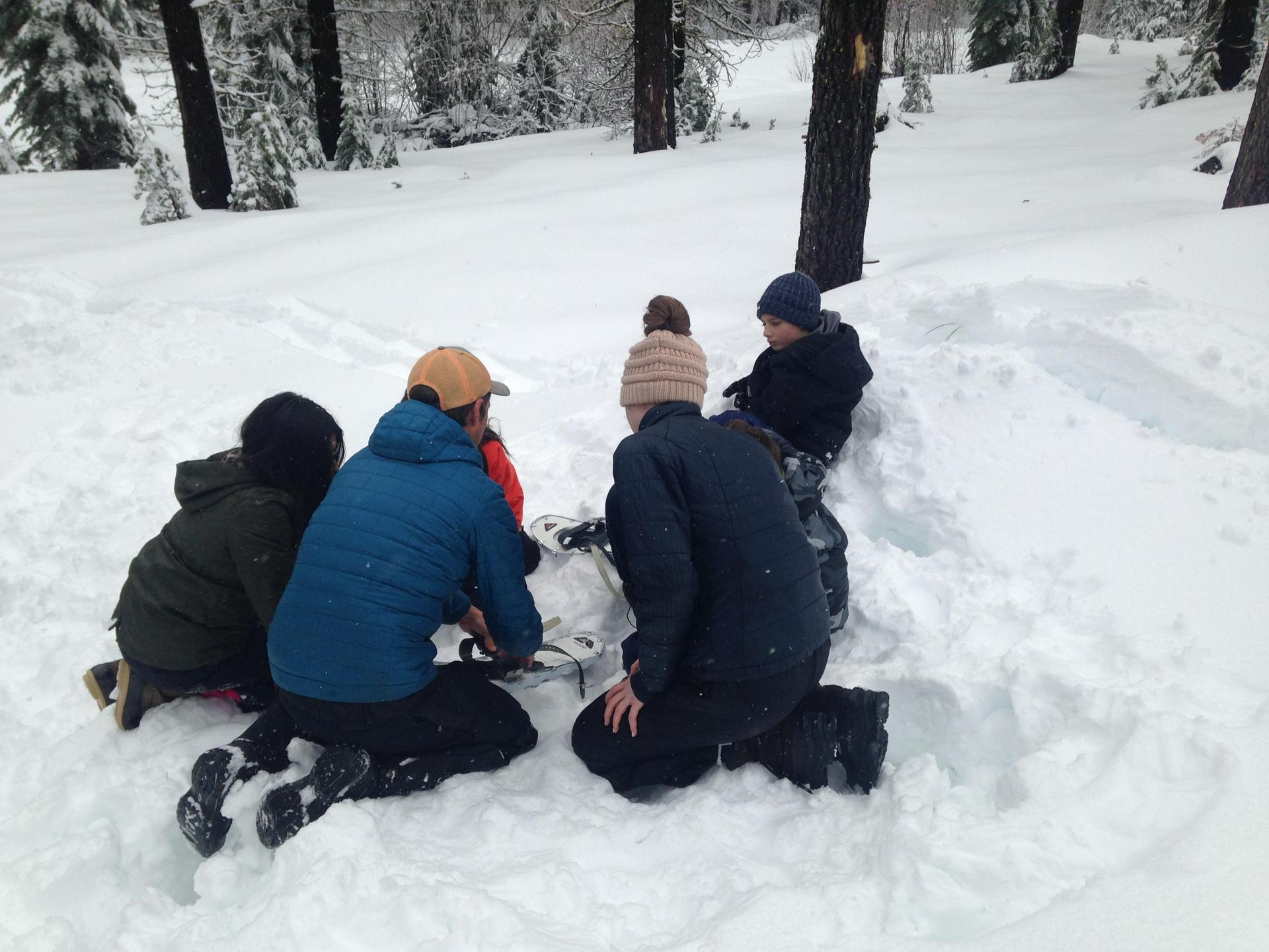 Kids putting on snowshoes