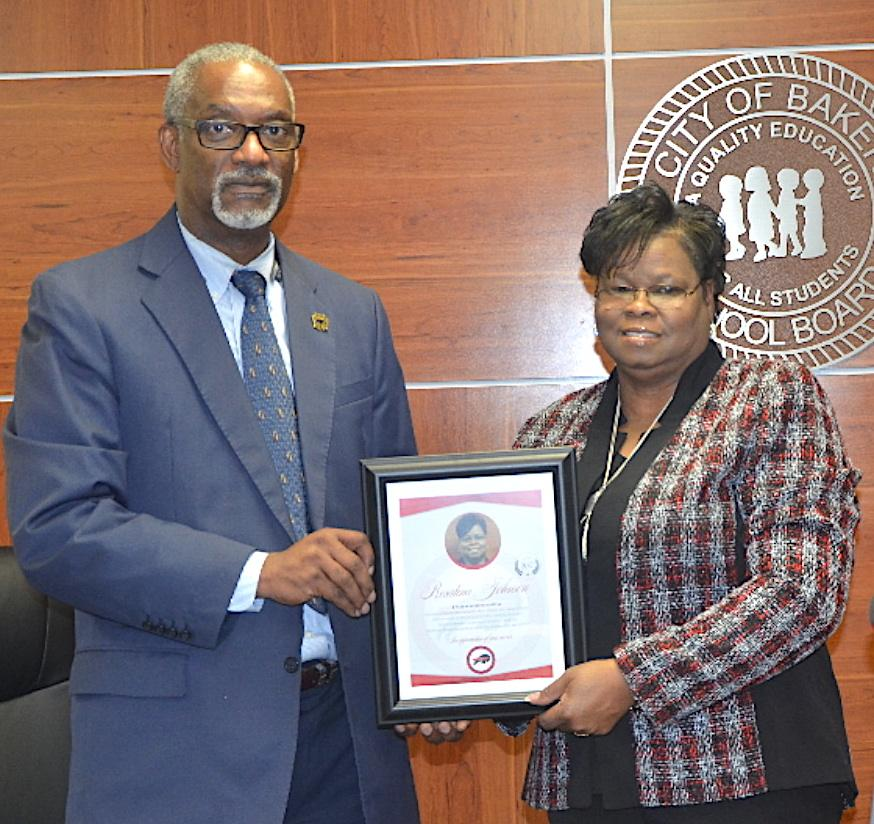 Photo of School System President Dr. Herman Brister presenting an award to outgoing Board Chairman Rosatina Johnson thanking her for service at the board's meeting on Tuesday.