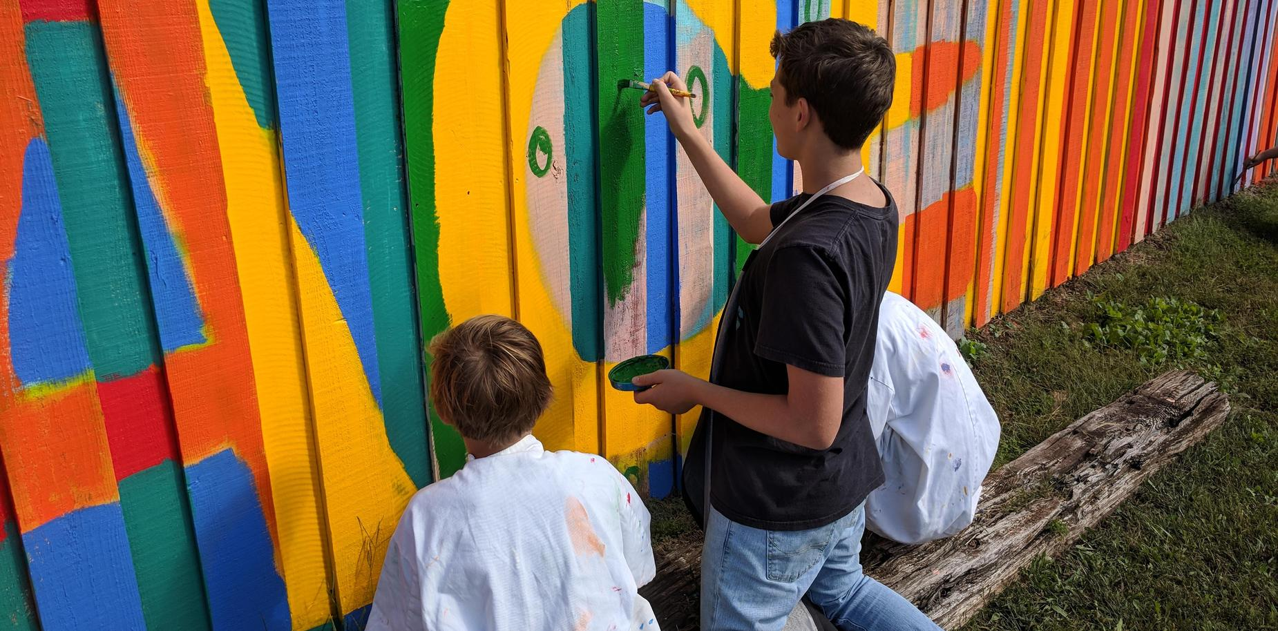 Students paint a colorful fence