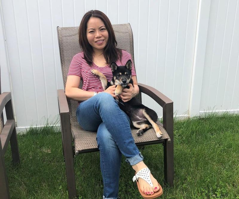 woman sits by fence with dog on her lap on chair