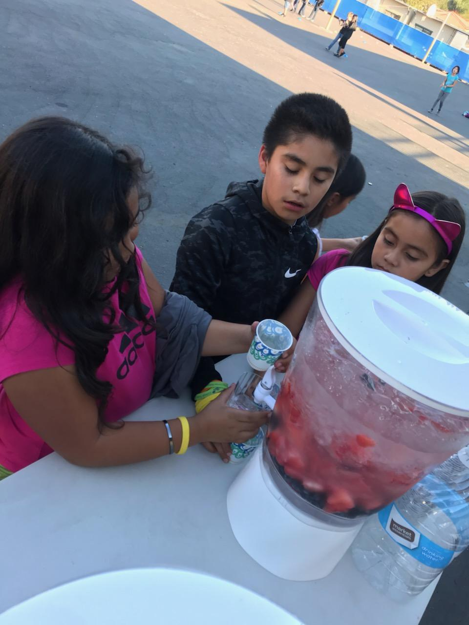 girl getting fruit-infused water from a dispenser